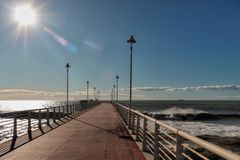 The pier between the breakers. In a clear winter morning after two stormy days stock photos