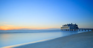 Pier and building on sea and beach. Follonica, Tuscany Italy. Pier and building on sea water and beach. Panoramic long exposure photography in Follonica travel Stock Images
