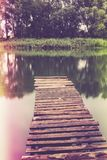 Pier on a calm river in the summer. Wooden pier bridge royalty free stock photos