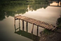 Pier on a calm river in the summer. Wooden pier bridge royalty free stock image