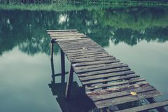 Pier on a calm river in the summer. Wooden pier bridge royalty free stock photography
