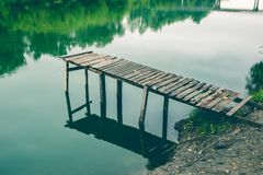 Pier on a calm river in the summer. Wooden pier bridge stock image