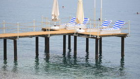 Pier with chaise longues in the sea in resort. Pier with chaise longues in the sea in Kemer resort in Turkey. Summer vacation. Calm sea and nobody on the stock video footage