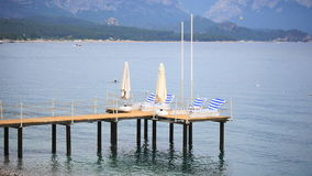 Pier with chaise longues in the sea in resort. Pier with chaise longues in the sea in Kemer resort in Turkey. Summer vacation. View at a calm sea and beautiful stock footage