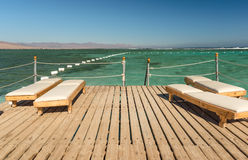Pier with chaise longues in the sea in resort. Royalty Free Stock Photos