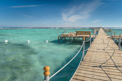 Pier with chaise longues in the sea in resort. Summer vacation. View at a clear sea with turquoise water. Summer vacation at a sea Royalty Free Stock Photo