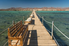Pier with chaise longues in the sea in resort. Summer vacation. View at a clear sea with turquoise water. Summer vacation at a sea Stock Photo