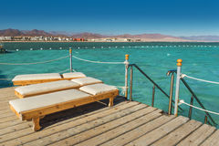 Pier with chaise longues in the sea in resort. Summer vacation. View at a clear sea with turquoise water. Summer vacation at a sea Royalty Free Stock Images