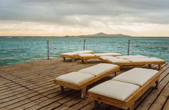 Pier with chaise longues in the sea in resort. Summer vacation. Royalty Free Stock Images