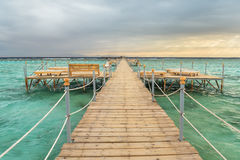 Pier with chaise longues in the sea in resort at sunset. Summer vacation. View at a clear sea with turquoise water. Summer vacatio Stock Image