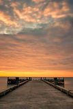 Pier and Cloudy Sunrise. Lonely Pier at Sunrise with cloudy condition Royalty Free Stock Photos
