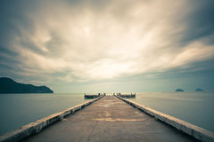 Pier & Cloudy Sunrise. Lonely pier with dramatic cloudy while sunrise Stock Photo