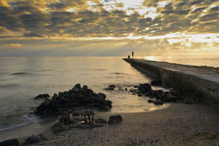 Pier on the coast . Pier with a fisherman on the coast against the dawn. Landscape Royalty Free Stock Photography