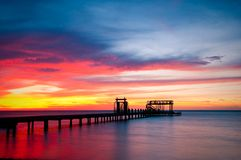 Pier and colorful ocean sunset. Long pier receding into sea with colorful sunset background royalty free stock image