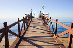 Pier on Costa del Sol in Marbella. Wooden pier in good condition with barriers and lanterns on a calm Mediterranean Sea in Marbella, Costa del Sol, Andalusia stock photos