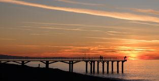 A pier with a couple and single silhouettes. With striped sky Stock Images