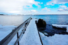Pier covered with snow and flozen sea melting Stock Images