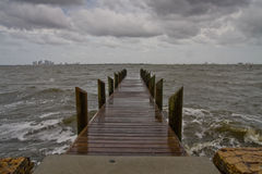 Pier on a Dark and Stormy Afternoon - Horizontal. Horizontal oriented image of a wooden pier on a dark and stormy afternoon with looming dark clouds stock image