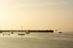 Pier at dawn. Pier silhouetted against the morning mist - Port Phillip Bay, Victora, Australia Stock Image