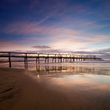 Pier at dawn with interesting reflections Stock Photos