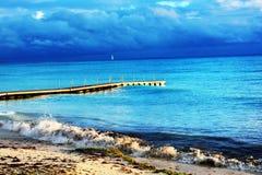 Pier, der den Ozean mit einem bewölkten Himmel verlässt stockfotos