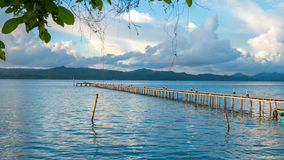 Pier of Dive Station - Kri Island. Clound above Gam in Background. Raja Ampat, Indonesia, West Papua. Pier of Dive Station on Kri Island. Clound above Gam Island Royalty Free Stock Photography