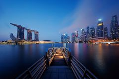 Pier in Downtown Singapore city in Marina Bay area. Financial district and skyscraper buildings at night stock photos