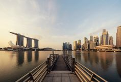 Pier in Downtown Singapore city in Marina Bay area. Financial district and skyscraper buildings at sunrise royalty free stock photos