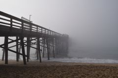 Pier extending into the Fog. Balboa Pier disappears into the fog in Newport Beach California stock photos