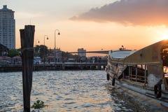 Pier für das Reisen entlang Chao Phraya River auf regelmäßiger Stadtbootslinie in Bangkok während des schönen Sonnenuntergangs Stockbild