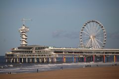 Pier and Ferris wheel at the beach of Scheveningen close to The Hague on the North sea beach.  royalty free stock photos