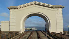 Pier 43 Ferry Arch with Jeremiah O'Brien warship at Pier 45 in F. SAN FRANCISCO - MAY 21 2015:Pier 43 Ferry Arch with Jeremiah O'Brien warship at Pier 45 in Stock Photos