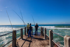 Pier Fishermen Rods Blue Waves. Local Fishermen end of  pier fishing on a clear blue morning with ocean waves Stock Photography