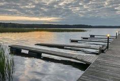 Pier for fishing boats, sunrise at Lilaste lake, Latvia Stock Photos