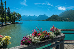 Pier with flowers on the lake of Annecy, in the village of Talloires. Mountains landscape and blue sky on background. France Stock Image