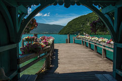 Pier with flowers on the lake of Annecy, in the village of Talloires. Mountains landscape and blue sky on background. France Royalty Free Stock Photo