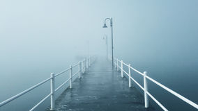 Pier in the fog. In a winter day stock image