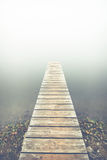 Pier in fog. Wooden pier at the foggy lake royalty free stock image