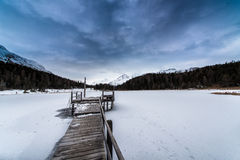 Pier on frozen lake Stock Photos