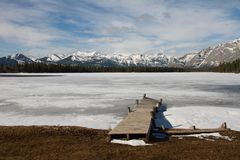 Pier into a frozen Lake in the Mountains. An old crooked wooden pier goes out into an ice covered lake in the mountains royalty free stock images