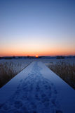 A pier by a frozen lake at sunset stock images