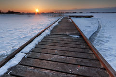 Pier through frozen lake Stock Images
