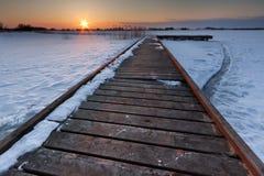 Pier through frozen lake Stock Images