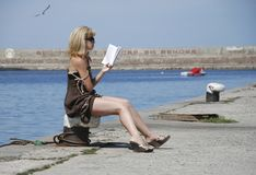 On the pier girl reading a book and sunbathing. In the sun, beauty royalty free stock photo