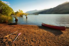 A Canoe on the side of the lake at Glenorchy Wharf, NZ. The Pier at Glenorchy Wharf with a Canoe on the side of the lake and the mountain range in the distance Royalty Free Stock Image