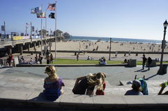 The Pier at Huntington Beach. People are gathered all over Huntington Beach to enjoy the summertime swimming and sight seeing Royalty Free Stock Photo