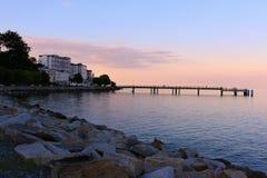 Pier im ruhigen See nach Sonnenuntergang lizenzfreie stockbilder