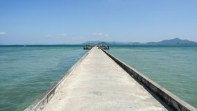 Pier at the indian ocean on the Koh muk Island. Harbor pier at the Koh Muk Island in Thailand with the blue sky and emerald waters Stock Image
