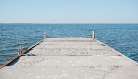 Pier from iron and concrete against the background of a river royalty free stock image