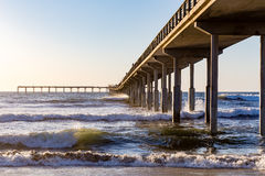Pier Jetting into the Sea. This long pier heads out over the ocean surf.  A falling sun backlights the rolling surf Royalty Free Stock Photo